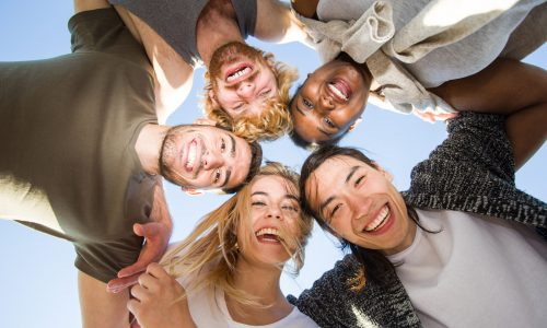 Cheerful friends huddling against blue sky on sunny day